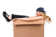 Fille s'asseyant dans une boîte en carton Photographie stock libre de droits