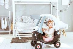 Fille s'asseyant dans une voiture de jouet Photo stock