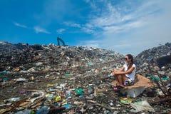 Fille s'asseyant dessus près de la route à la décharge de déchets images stock