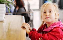 Fille s'asseyant en café Image libre de droits