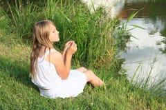 Fille s'asseyant par l'étang Photos libres de droits