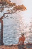 Fille s'asseyant par le flanc de coteau de mer au coucher du soleil Photographie stock libre de droits
