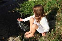 Fille s'asseyant par une rivière Photographie stock libre de droits