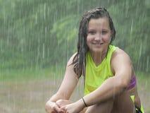Fille s'asseyant sous la pluie Photographie stock