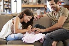 Fille s'asseyant sur des clous du ` s de Sofa At Home Painting Father image stock