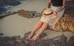 Fille s'asseyant sur des pierres sur le rivage de la mer de matin, tenant dessus ses genoux un chapeau de paille Utilise une long Photographie stock