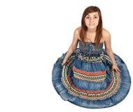 Fille s'asseyant sur l'étage dans la robe de denim photo libre de droits