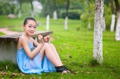Fille s'asseyant sur l'herbe image stock