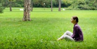 Fille s'asseyant sur l'herbe Photo libre de droits