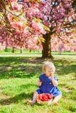 Fille s'asseyant sur l'herbe et mangeant des fraises image libre de droits