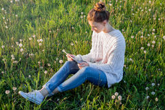 Fille s'asseyant sur l'herbe et regardant la tablette Photos libres de droits