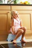 Fille s'asseyant sur l'opération en plastique dans la cuisine image libre de droits