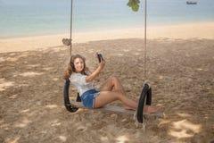 Fille s'asseyant sur l'oscillation sur la plage tropicale Image stock