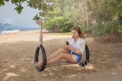 Fille s'asseyant sur l'oscillation sur la plage tropicale Images libres de droits