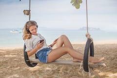 Fille s'asseyant sur l'oscillation sur la plage tropicale Image libre de droits