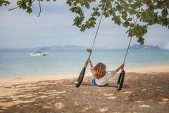 Fille s'asseyant sur l'oscillation sur la plage tropicale Photo stock