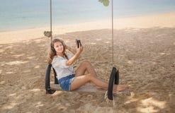 Fille s'asseyant sur l'oscillation sur la plage tropicale Images stock