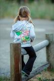 Fille s'asseyant sur la barrière Images libres de droits