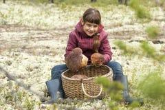 Fille s'asseyant sur la mousse dans la forêt avec le panier des champignons Images libres de droits