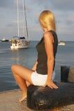 Fille s'asseyant sur la plage Photos libres de droits