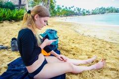 Fille s'asseyant sur la plage avec le smartphone images libres de droits