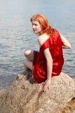 Fille s'asseyant sur la roche Photographie stock libre de droits