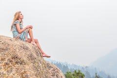 Fille s'asseyant sur la roche Image stock