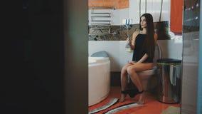 la femme avec les jambes nues marchent dans la salle de bains et s asseyent sur la toilette