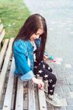 Fille s'asseyant sur le banc avec des sucreries Image stock