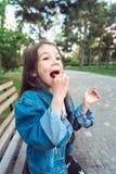 Fille s'asseyant sur le banc avec des sucreries Photo libre de droits