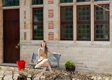 Fille s'asseyant sur le banc devant la maison antique Image libre de droits