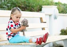 Fille s'asseyant sur le banc et le jouet de caresse de singe photo libre de droits