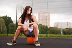 Fille s'asseyant sur le basket-ball Photographie stock