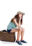 Fille s'asseyant sur le cas partant en voyage, fond blanc Photos stock