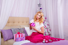Fille s'asseyant sur le divan et préparant des cadeaux de Noël Image stock