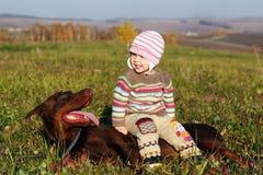 Fille s'asseyant sur le dobermann Photo stock