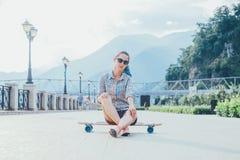 Fille s'asseyant sur le longboard extérieur Photo libre de droits