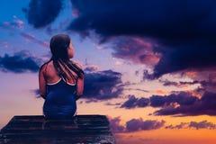 Fille s'asseyant sur le pilier en bois et regardant en ciel images libres de droits