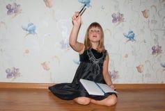 Fille s'asseyant sur le plancher avec le carnet et le stylo Photographie stock
