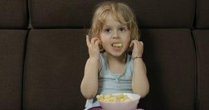 Fille s'asseyant sur le sofa et mangeant des souffles de ma?s Puffcorns de go?t d'enfant image stock