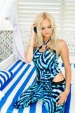 Fille s'asseyant sur son recouvrement dans des combinaisons bleues Photo stock