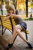 Fille s'asseyant sur un banc Photographie stock