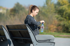 Fille s'asseyant sur un banc de parc Image libre de droits