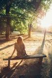 Fille s'asseyant sur un banc de parc Images libres de droits