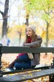 Fille s'asseyant sur un banc en parc un jour d'automne Images stock