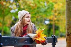 Fille s'asseyant sur un banc en parc un jour d'automne Images libres de droits