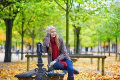 Fille s'asseyant sur un banc en parc un jour d'automne Photos libres de droits