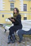 Fille s'asseyant sur un banc et affichant un livre Photographie stock libre de droits