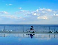 Fille s'asseyant sur un canapé par la piscine et la mer Image stock