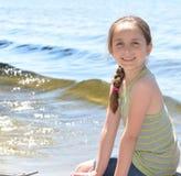 Fille s'asseyant sur un dock Images stock